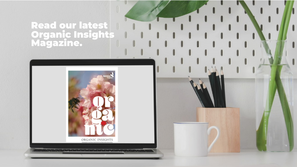 A clean white desk features a green plant and a Macbook Pro with an image of NASAA Organic's Organic Insights on the screen